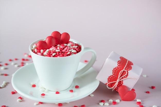 Świąteczne tło. filiżanka kawy, pełna kolorowych cukierków, posypuje serca cukierków cukrowych i pakuje prezenty walentynkowe. koncepcja miłości i walentynki.