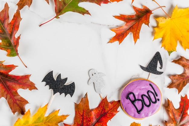 Świąteczne tło na halloween, biały marmurowy stół z piernikowym ciastkiem z napisem boo !, symbolami świątecznymi (nietoperz, kapelusz czarownicy, duch) i jesiennymi czerwonymi żółtymi liśćmi, widok z góry
