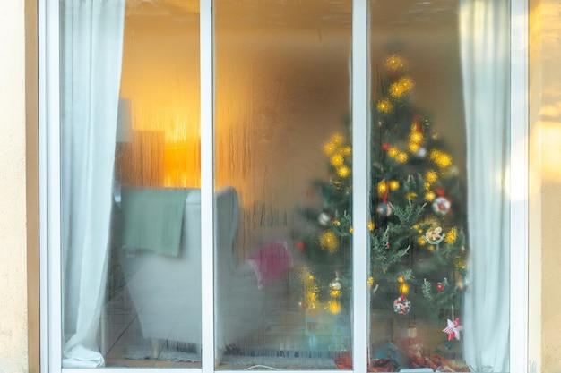 Świąteczne tło okna i piękna ozdobiona choinka ze światłami i błyszczącymi kulkami
