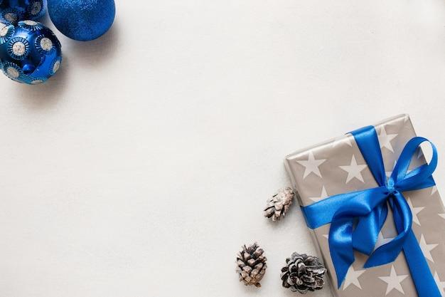 Świąteczne tło prezentów świątecznych. zapakowane pudełko, ozdobne niebieskie kulki i strobila leżące na białym stole w pobliżu, widok z góry z miejscem na kopię. ręcznie robiona koncepcja wystroju