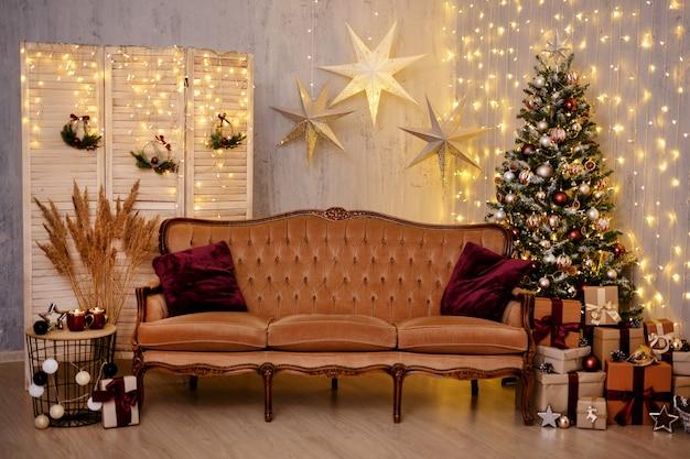 Świąteczne tło - udekorowany salon z choinką, sofą w stylu vintage, świątecznymi girlandami świateł i zapakowanymi pudełkami prezentowymi