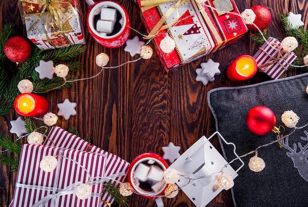 Świąteczne tło, w tym pudełka na prezenty, gorąca czekolada, gałęzie jodły i inne ozdoby na drewnianym stole