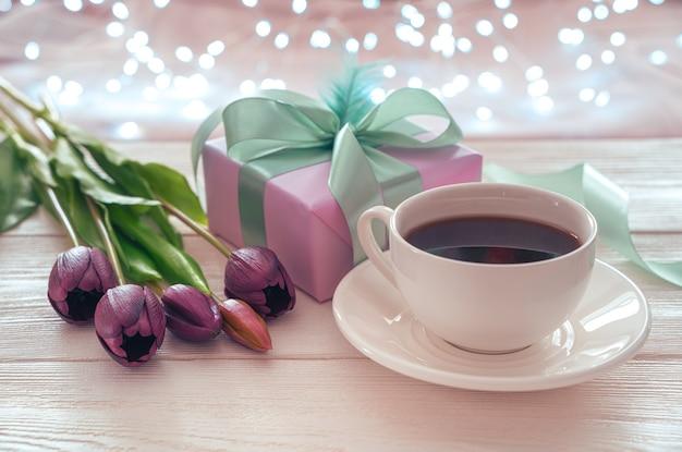 Świąteczne tło z filiżanką kawy, kwiatami i opakowaniem prezentów na tle płonącej girlandy. widok z boku. pojęcie tła wakacyjnego.
