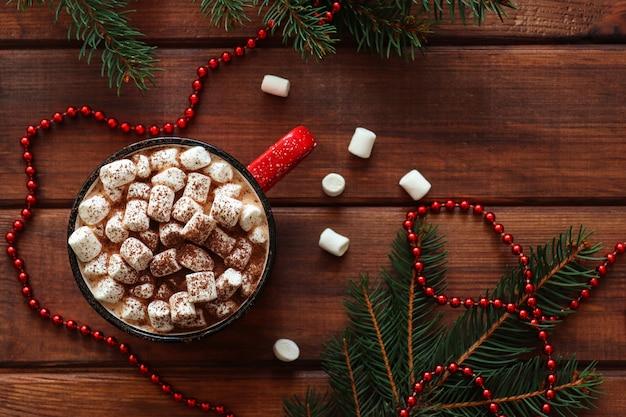 Świąteczne tło z gałęziami choinki i gorącą czekoladą z piankami na drewnianym stole