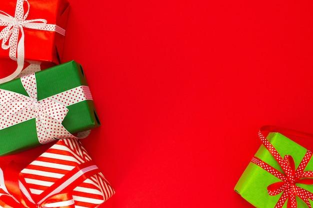 Świąteczne tło z kolorowymi prezentami, pudełka na prezenty ze wstążką i kokardą na czerwonym tle, płaski świecki, widok z góry, puste miejsce na tekst