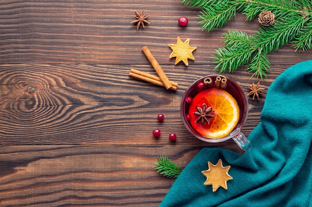 Świąteczne tło z kubkiem grzanego wina obok turkusowego szalika na drewnianym stole