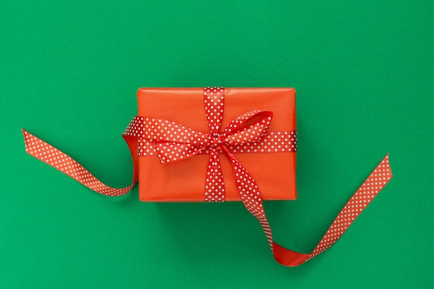 Świąteczne tło z prezentem, czerwone pudełko ze wstążką w kropki i kokardą na zielonym tle, płaskie lay, widok z góry