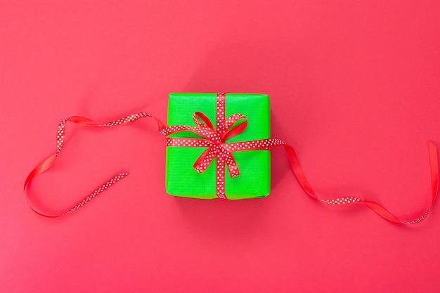 Świąteczne tło z prezentem, zielone pudełko ze wstążką i kokardą na różowym tle, leżał płasko, widok z góry