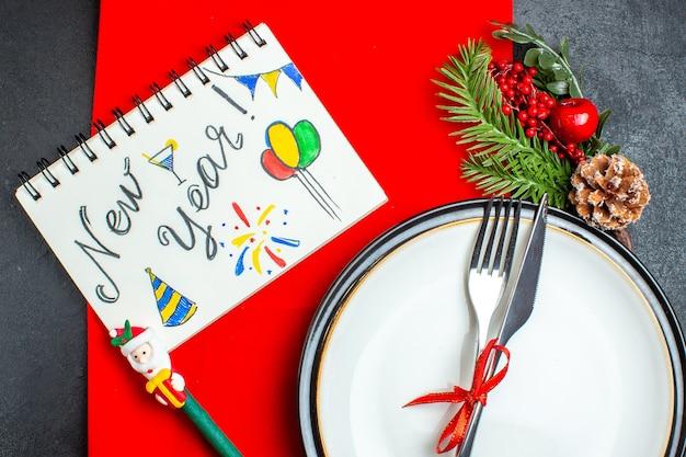 Świąteczne tło z zestawem sztućców z czerwoną wstążką na talerzu obiadowym akcesoria do dekoracji gałązki jodły obok notatnika z długopisem na czerwonej serwetce