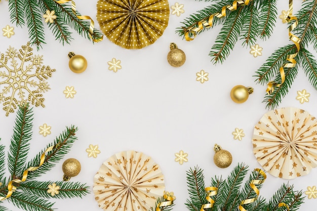 Świąteczne tło ze złotą dekoracją, zielonymi gałązkami świerkowymi i pudełkami na prezenty, papierowymi dekoracjami na choinkę, błyszczącymi płatkami śniegu i bombkami