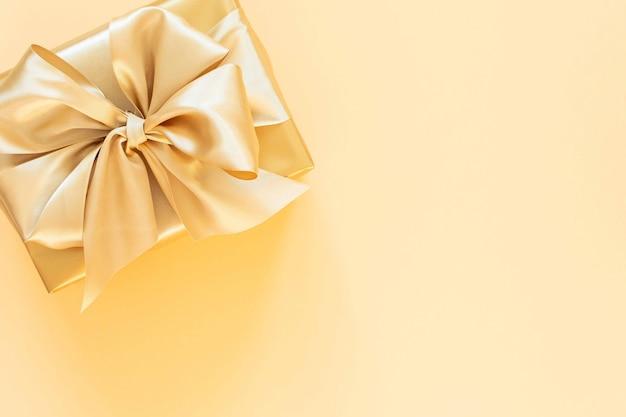 Świąteczne tło ze złotym prezentem, pudełko ze wstążką i kokardą na złotym tle, płaskie świecenie, widok z góry, miejsce na kopię