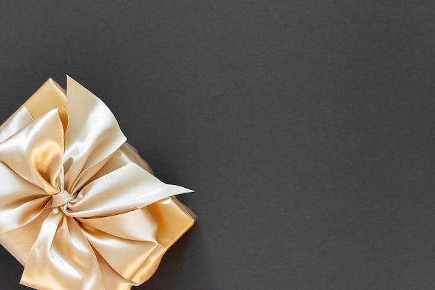 Świąteczne tło ze złotym prezentem, pudełko ze złotą wstążką i kokardą na czarnym tle, płaskie ułożenie, widok z góry, miejsce na kopię