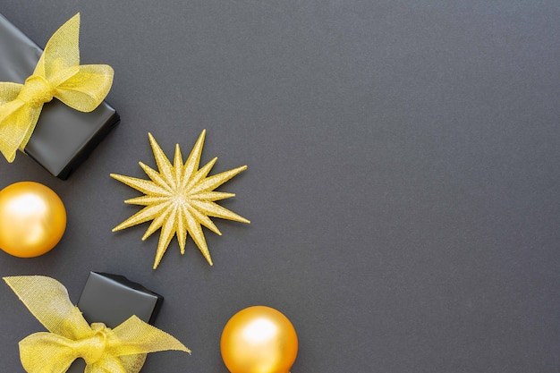 Świąteczne tło ze złotymi dekoracjami, błyszczącą złotą gwiazdą i pudełkami prezentowymi oraz bombkami na czarnym tle, płaskie świecenie, widok z góry, kopia przestrzeń