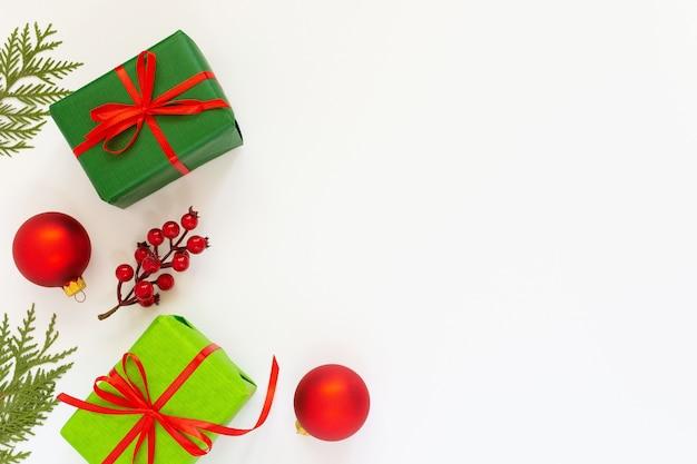 Świąteczne tło, zielone pudełka z czerwonymi wstążkami i gałąź głogu