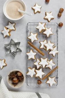 Świąteczne tradycyjne niemieckie ciasteczka, cynamonowe gwiazdki z orzechami laskowymi na jasnej betonowej powierzchni
