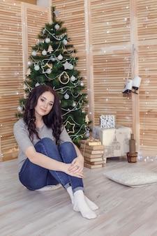 Świąteczne uczucie. po wigilii. dziewczyny z uśmiechniętymi twarzami w pobliżu choinki na drewnianej ścianie.