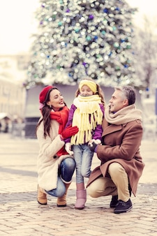 Świąteczne weekendy. zachwycona długowłosa kobieta z uśmiechem na twarzy, patrząc na swoje dziecko