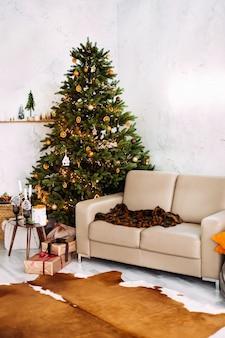 Świąteczne wnętrze domu z sofą ozdobioną choinką, sofą, stołem ze świecami i dekoracjami.