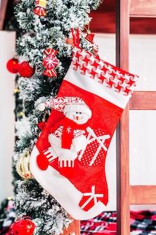 Świąteczne wnętrze pokoju z ozdobionymi czerwonymi świątecznymi skarpetkami i choinką oraz drewniane łóżko stylowe wnętrze dziecięcego pokoju.