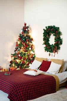 Świąteczne wnętrze sypialni w biało-czerwonych kolorach. podwójne łóżko z kocem w kratę i choinką