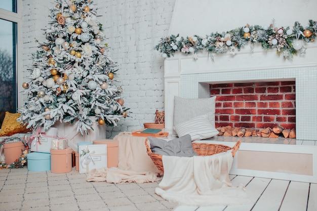 Świąteczne wnętrze w białych kolorach. biała drewniana podłoga, choinka z ozdobami, prezenty i kominek. świąteczna przytulność.