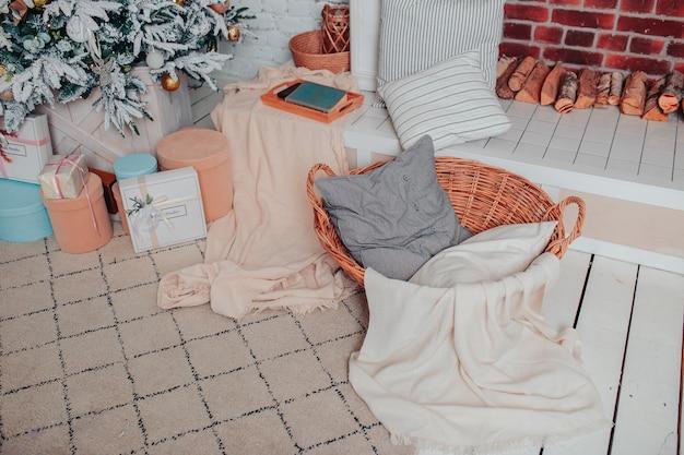 Świąteczne wnętrze w białych kolorach. biała drewniana podłoga, choinka z ozdobami, prezenty, kominek i kosz. świąteczna przytulność.