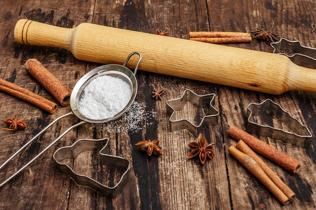 Świąteczne wypieki, wyroby piekarnicze, przyprawy, foremki do ciastek - gwiazdki, anioł i jodła, sito, cukier w proszku i wałek do ciasta. stare drewniane deski