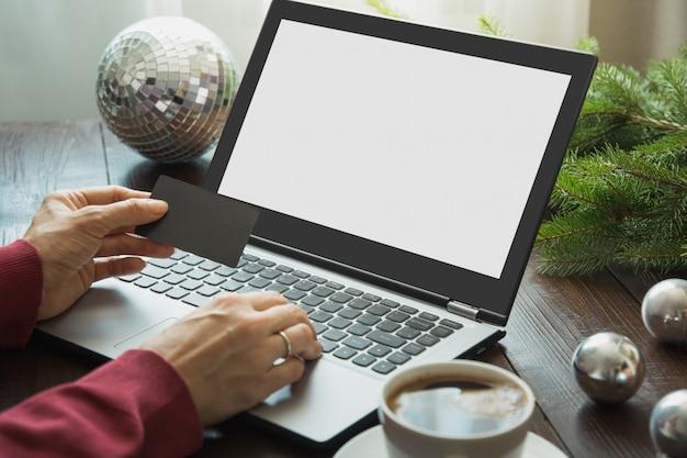 Świąteczne wyprzedaże, kobieta zakupy kartą kredytową przez laptopa w domowym wnętrzu.