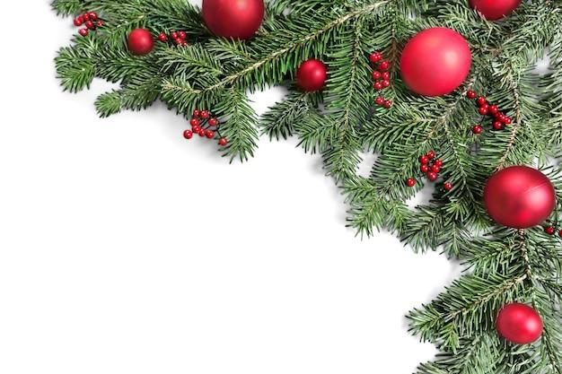 Świąteczne zabawki na gałęzi jodły, na białym tle