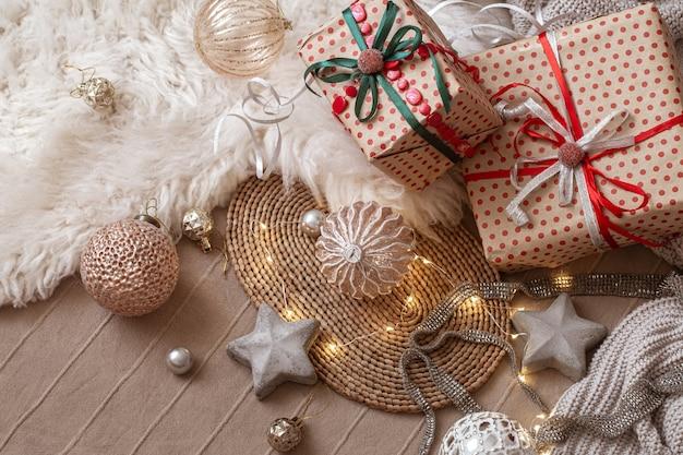 Świąteczne zabawki, ozdobne gwiazdki, zapakowane prezenty i girlanda na tle wnętrza domu.