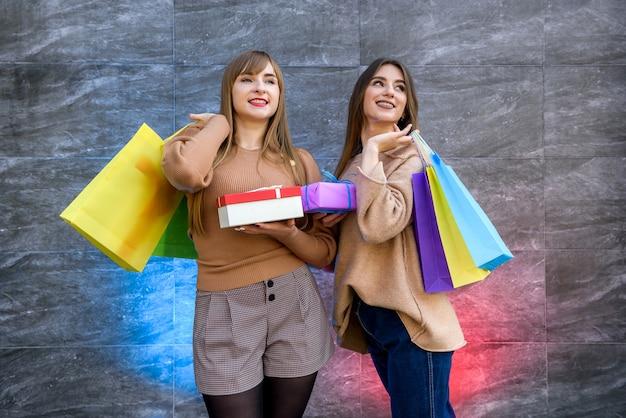 Świąteczne zakupy. dwie szczęśliwe kobiety z kolorowymi torebkami na prezenty pozują po zakupach