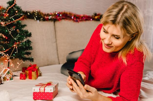 Świąteczne zakupy online. kobieta kupująca składa zamówienie na telefon komórkowy. kobieta kupuje prezenty, przygotowuje się do świąt, pudełko w ręku. wyprzedaż ferii zimowych.