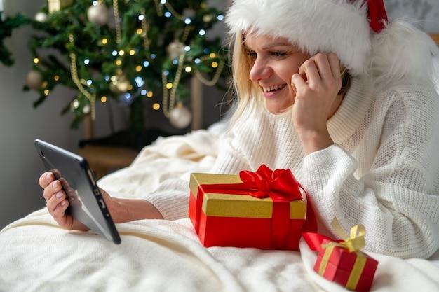 Świąteczne zakupy online. kobieta kupująca składa zamówienie na telefon komórkowy. kobieta kupuje prezenty, przygotowuje się do świąt, pudełko w ręku. wyprzedaż ferii zimowych