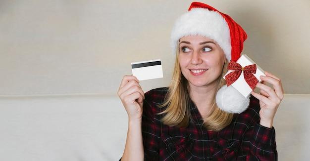 Świąteczne zakupy online. kobieta trzyma kartę i pudełko. kobieta ubrana w czerwony świąteczny kapelusz, kup prezenty, przygotowuje się do świąt bożego narodzenia.