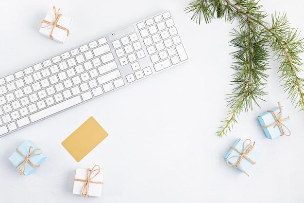 Świąteczne zakupy online z pudełkami na prezenty, klawiaturą i makietą złotej karty kredytowej