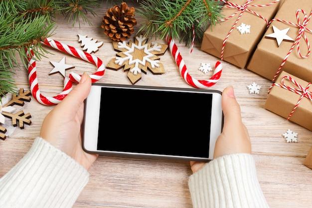 Świąteczne zakupy online. żeński nabywca robi rozkazowi przy ekranem smartphone z copyspace. kobieta kupuje prezenty na wigilię bożego narodzenia, siedzi w domu, w pobliżu ozdobiona. sprzedaż ferii zimowych