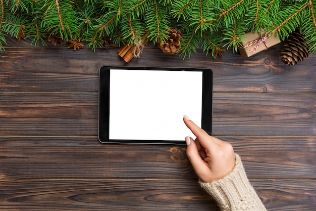 Świąteczne zakupy online. żeński ręka dotyka ekran pastylka, odgórny widok na drewnianym bakground, copyspace. tło sprzedaży ferie zimowe