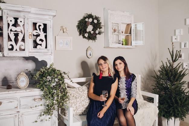 Świąteczne zdjęcia pięknych dziewczyn w wieczorowych sukienkach otoczone są prezentami