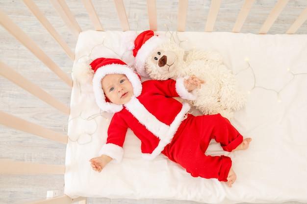 Świąteczne zdjęcie dziecka w stroju świętego mikołaja leżącego w łóżeczku w domu z zabawką w czapce świętego mikołaja