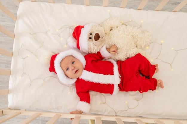 Świąteczne zdjęcie dziecka w stroju świętego mikołaja leżącego w łóżeczku w domu
