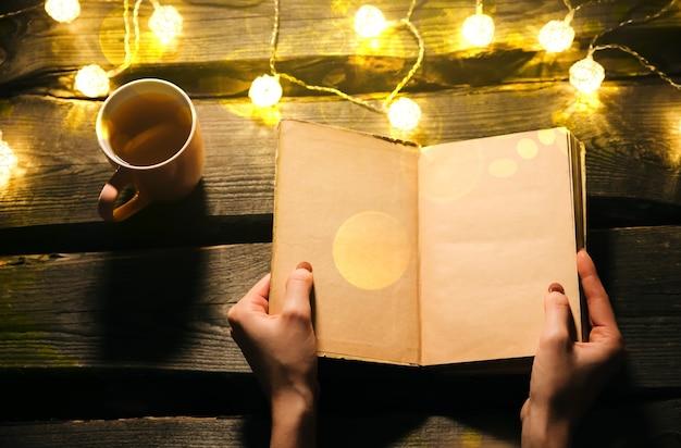 Świąteczne zdjęcie nastroju. lampki choinkowe i kubek gorącej herbaty. książka w rękach dziewczyny na przytulny wieczór. kobieta czytająca. idealny zimowy układ płaski. koncepcja hygge.