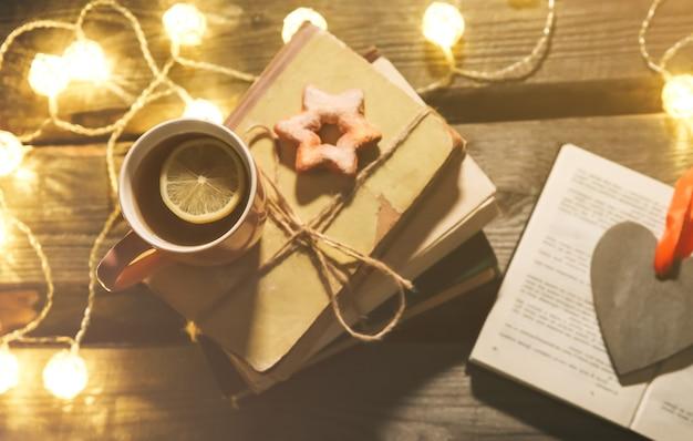 Świąteczne zdjęcie nastroju. lampki choinkowe i kubek gorącej herbaty. zarezerwuj na przytulny wieczór. słodki piernik i drewniane serce na tacy. idealne zimowe mieszkanie ze świecą. koncepcja hygge.