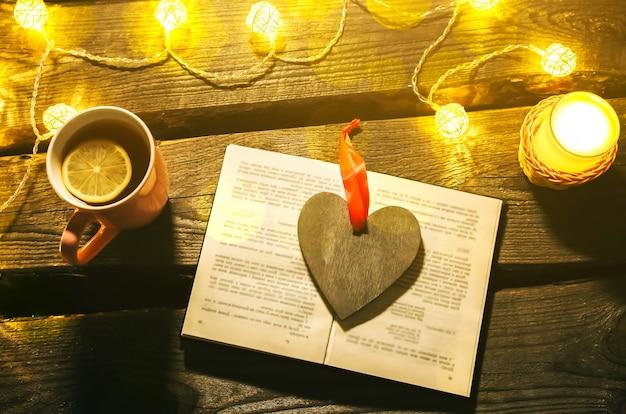 Świąteczne zdjęcie nastroju. lampki choinkowe i kubek gorącej herbaty. zarezerwuj na przytulny wieczór. słodki piernik i drewniane serce na tacy. idealny zimowy układ płaski. koncepcja hygge.