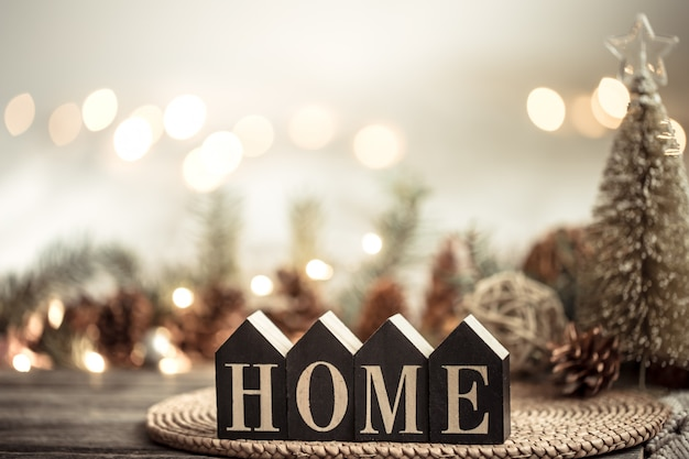 Świąteczne ze światłami i napisem do domu na drewnianym stole. z świątecznymi elementami dekoracyjnymi.