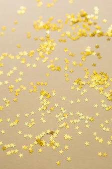 Świąteczne złote gwiazdy konfetti są rozrzucone na jasnym tle.