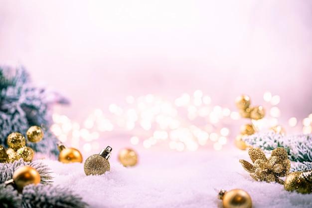 Świąteczne złote ozdoby na śniegu z gałęziami jodły i zimową dekoracją świątecznych świateł