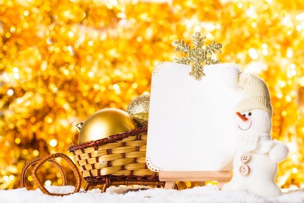 Świąteczne życzenia ze śniegiem, bałwanem i saniami na złotym, błyszczącym tle