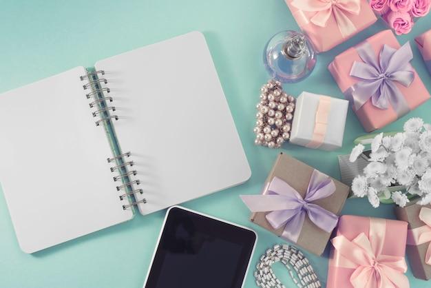 Świątecznego tła plakata pudełka prezenta atłasowy tasiemkowy łęku bukiet kwiaty biżuterii perły notatnika pastylki smartphone tła błękit.