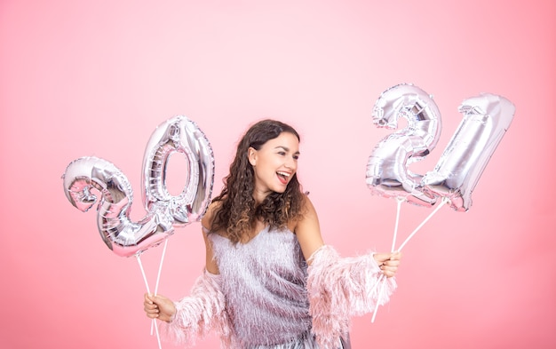 Świątecznie ubrana młoda dziewczyna, śmiejąc się na różowym tle ze srebrnymi balonami boże narodzenie dla koncepcji nowego roku