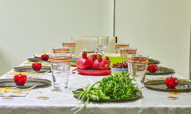 Świątecznie udekorowany stół na rosz ha-szana z granatami i jabłkami